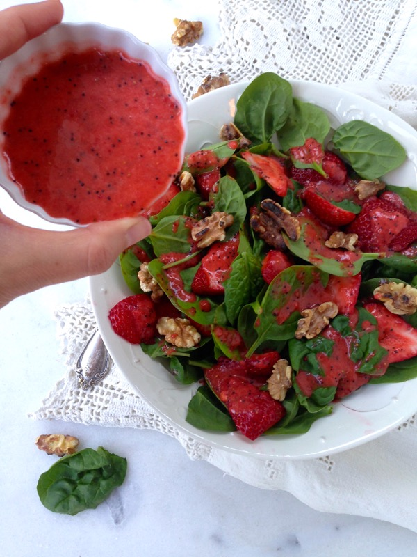 Strawberry Spinach Salad being drizzled with Poppy Seed Dressing