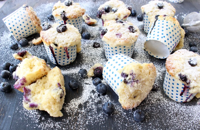 blueberry ricotta muffins in polka dot muffin cups on a wooden table