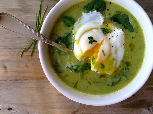 White bowl of green Broccoli Spinach Soup with a creamy poached egg on top