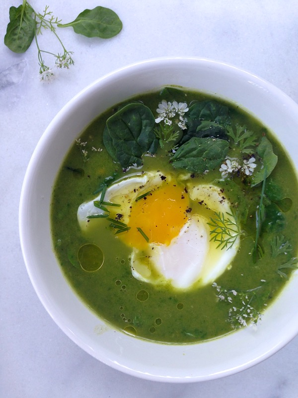 White bowl of green Broccoli Spinach Soup with a poached egg on top