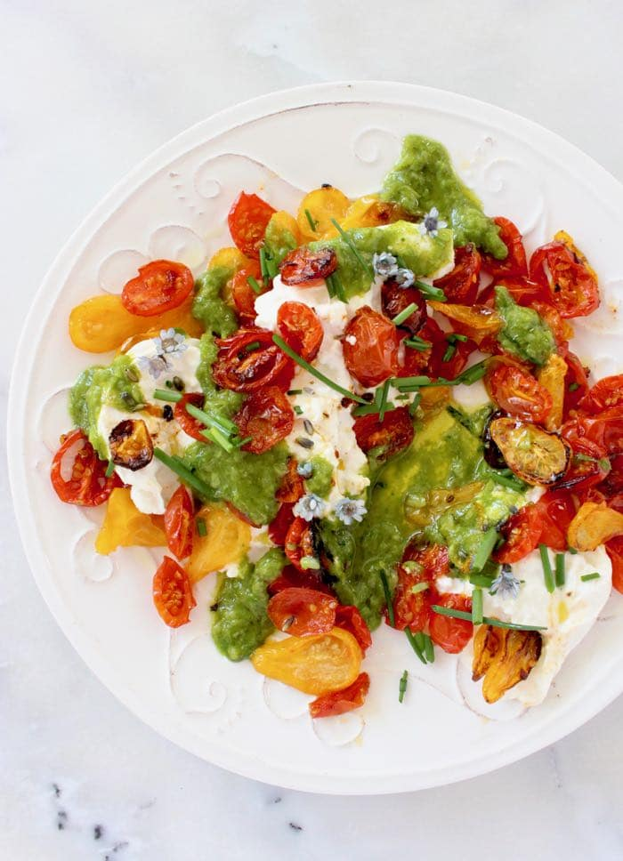 Platter of roasted cherry tomato salad with fresh burrata and scallion dressing