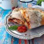 Chicken Stuffed Calzone with Arrabiata Sauce on a Rustic Table