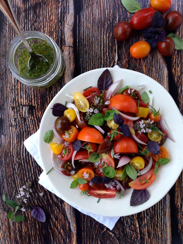 White Bowl Of Heirloom Tomato Basil Salad with Purple and Green Basils and Chive Blossoms