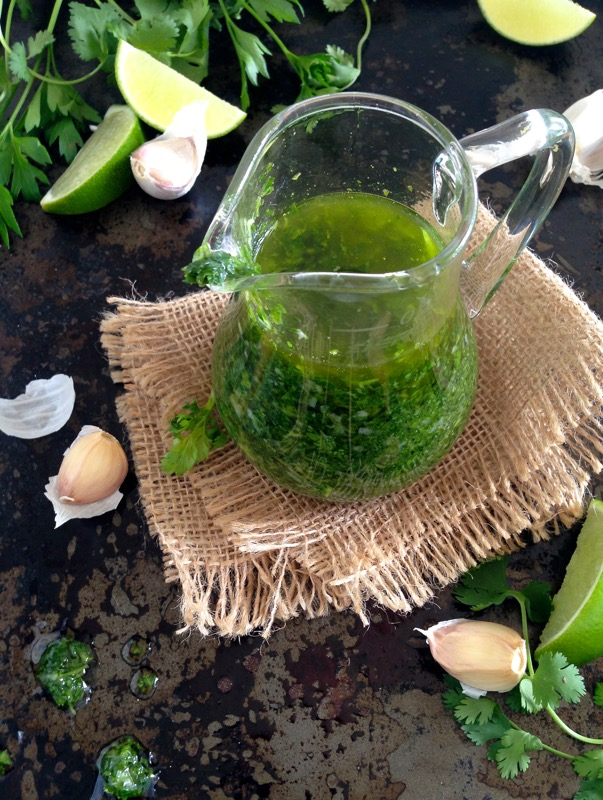 Glass pitcher with chimichurri on a black cookie sheet surrounded by garlic and limes