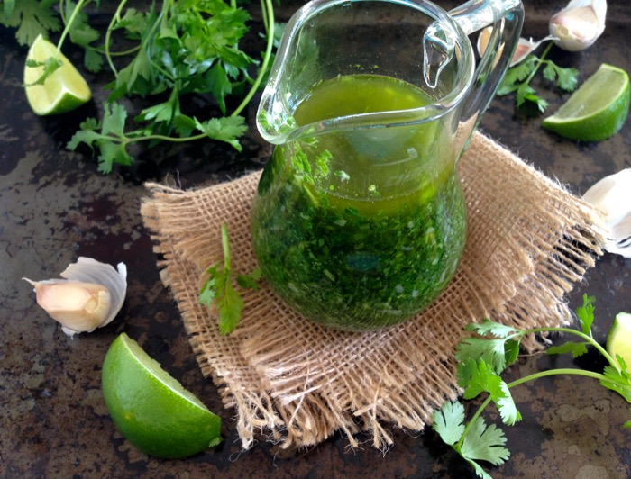 Glass pitcher filled with chimichurri surrounded by parsley and limes
