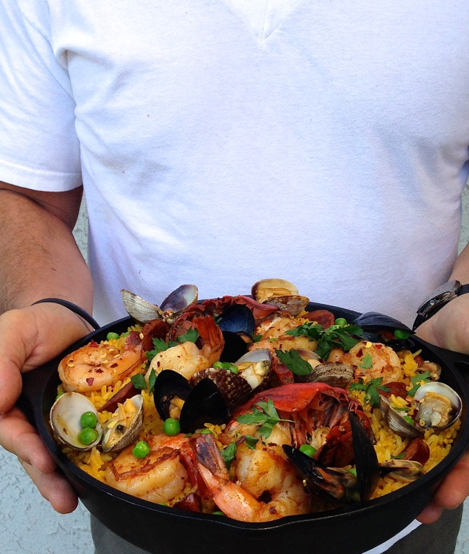 Man Holding A Seafood Spanish Paella in a Cast Iron Pan with Lobster and Shrimp