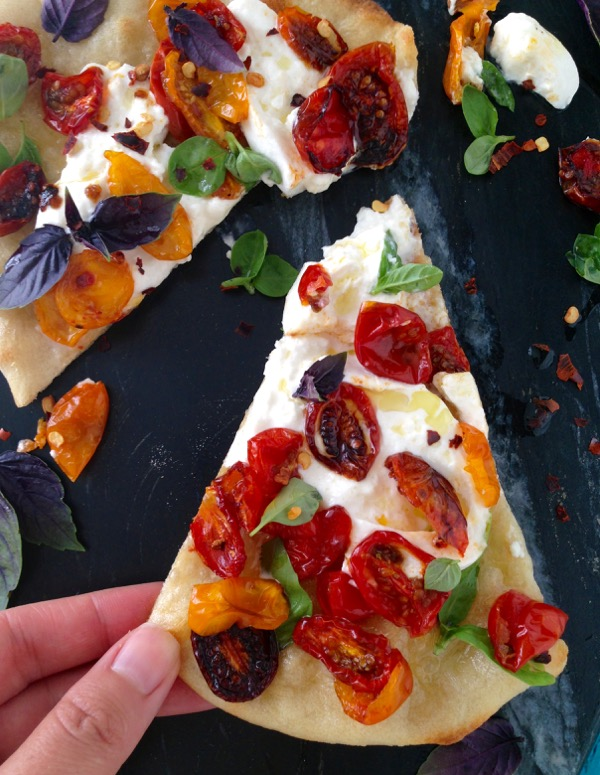 Slice of Burrata Pizza with Roasted Tomatoes and Basil on a Black Marble