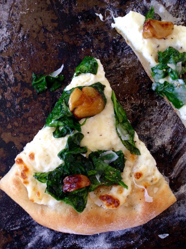 Slice of Ricotta Spinach Pizza with Roasted Garlic Cloves on a Distressed Cookie Sheet