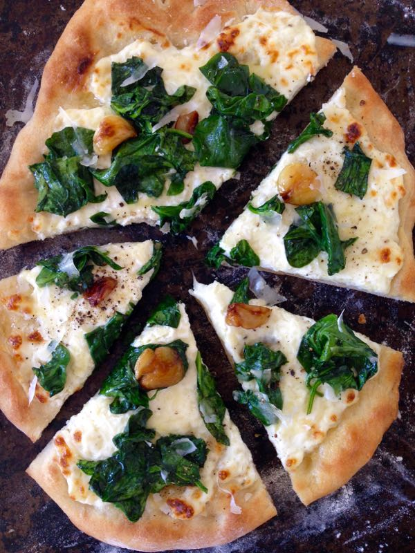 Sliced up pizza Bianca with Ricotta and Spinach on a distressed cookie sheet.