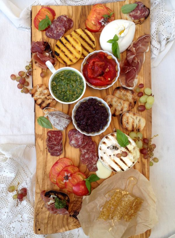 Olive wood bruschetta bar with pesto, tapenade, cheese, salami, fruit and roasted peppers