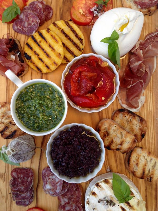 Olive wood bruschetta bar with pesto, tapenade, cheese and roasted peppers