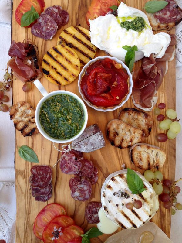 Bruschetta bar spread on a rustic olive wood board