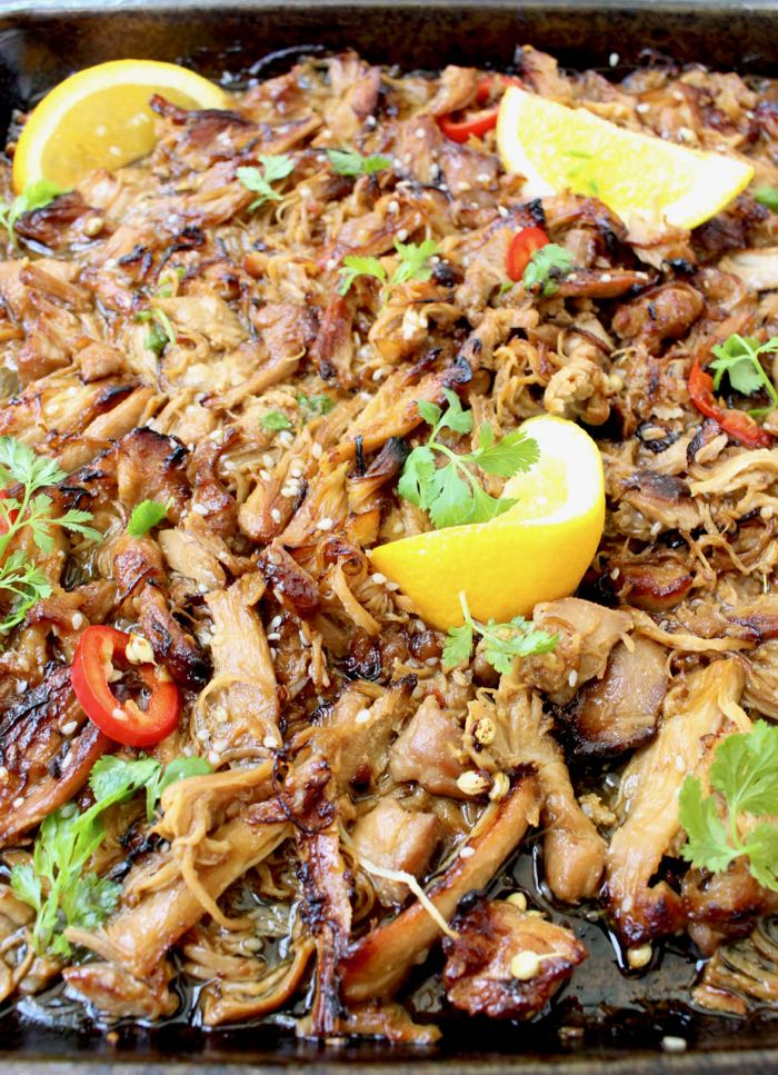 Tray of Asian style chicken carnitas with red chili and orange wedges