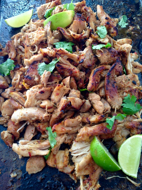 Baking sheet of chicken carnitas, cilantro and limes