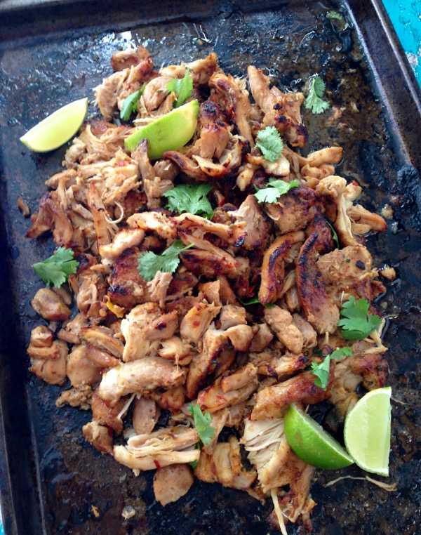 Black cookie sheet with shredded chicken carnitas and limes