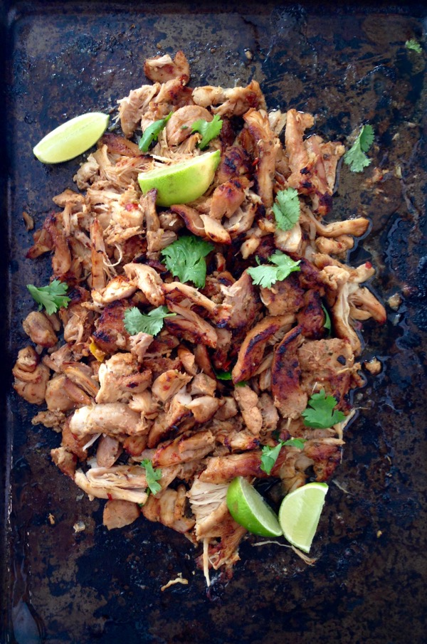 Black cookie sheet with shredded chicken carnitas