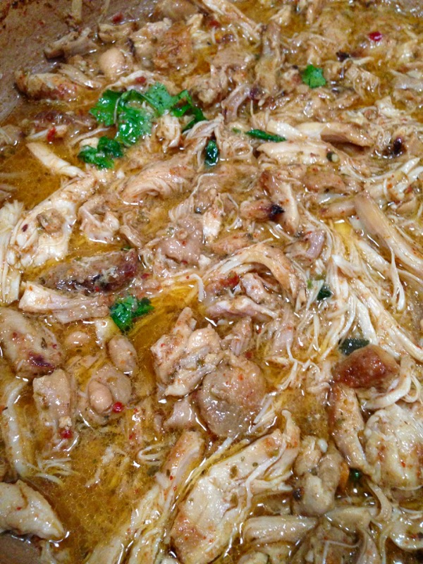 Pot of chicken carnitas cooking in gravy