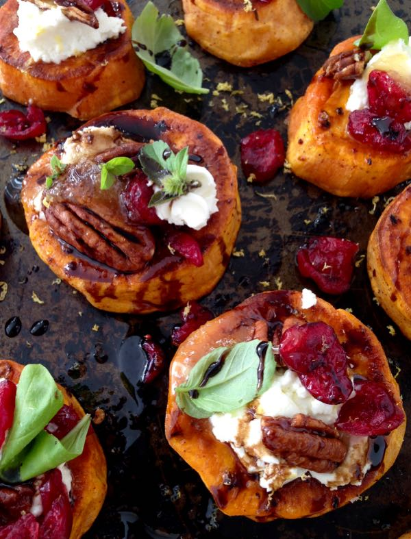 A Black Tray of Sweet Potato Appetizers, Topped with Goat Cheese, Candied Walnuts, Cranberries & Balsamic Glaze