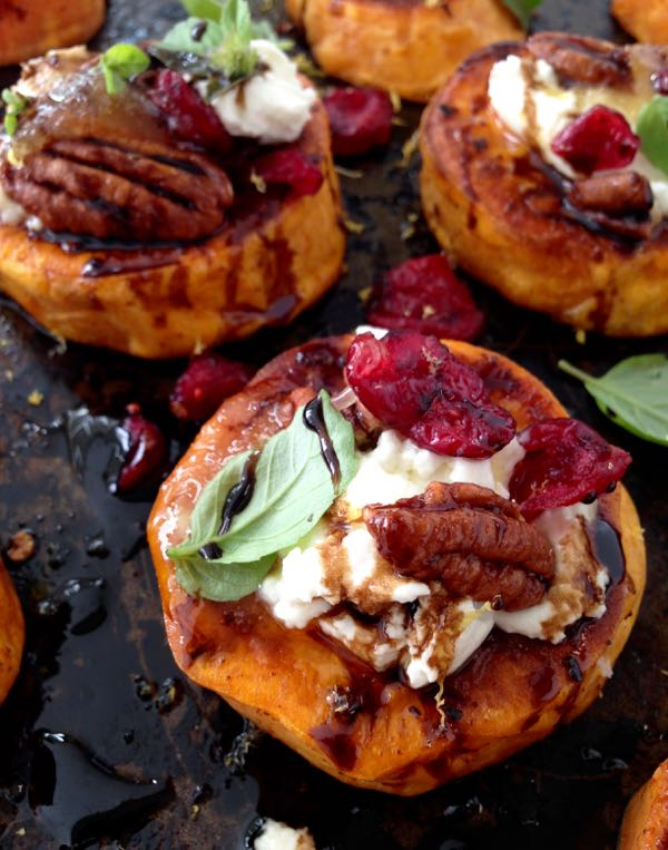 A Black Tray of Sweet Potato Appetizers Topped with Goat Cheese, Candied Walnuts, Cranberries & Balsamic Glaze