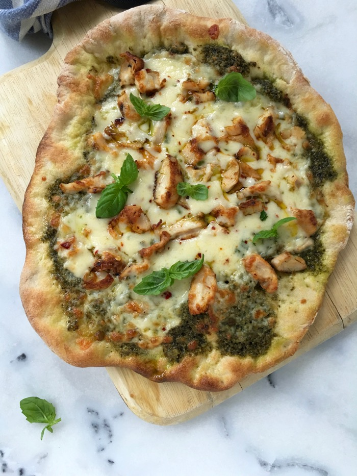 Chicken pesto pizza on a wooden board.
