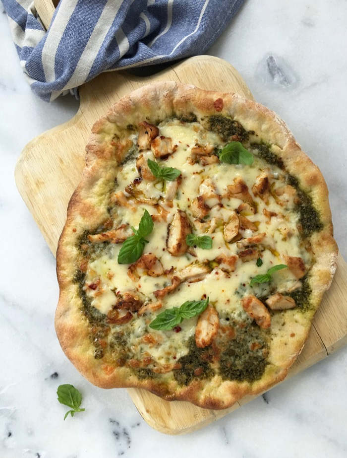 Crispy chicken pesto pizza with basil on a cutting board.