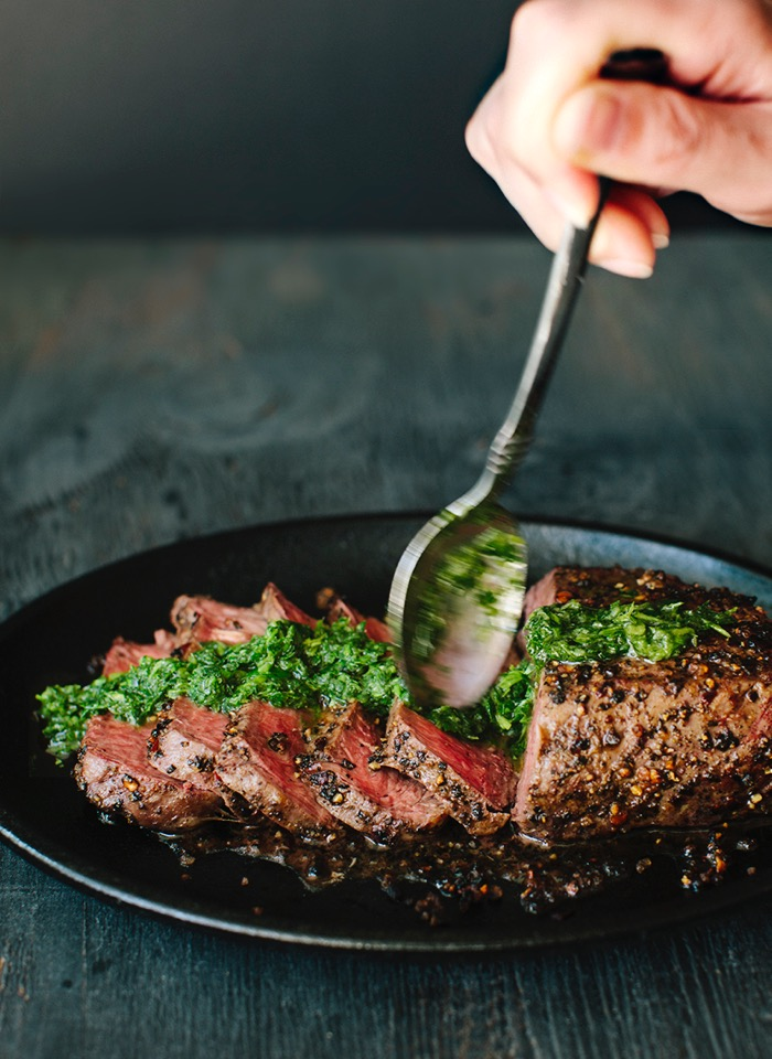 Sliced peppercorn crusted steak drizzled in chimichurri sauce in a cast iron skillet