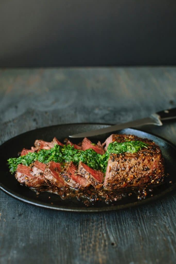 Sirloin Steak in a Cast Iron Skillet drizzled with Chimichurri Sauce