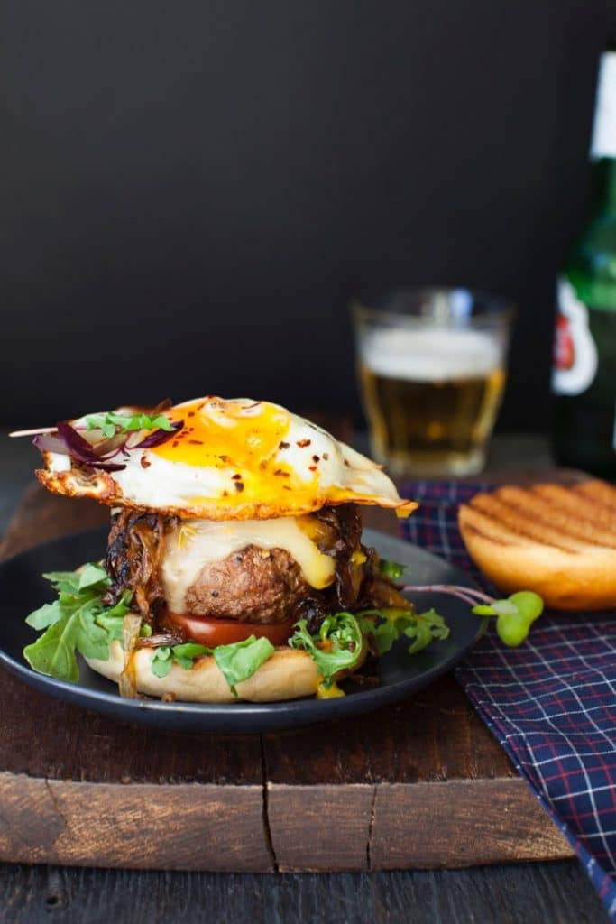 Breakfast Fried Egg Burger on a Wooden Table with a Glass of Beer