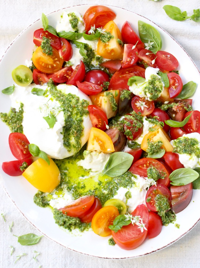 Colorful Heirloom Tomato Burrata Caprese Salad on a white Platter with Drizzles of Basil Pesto