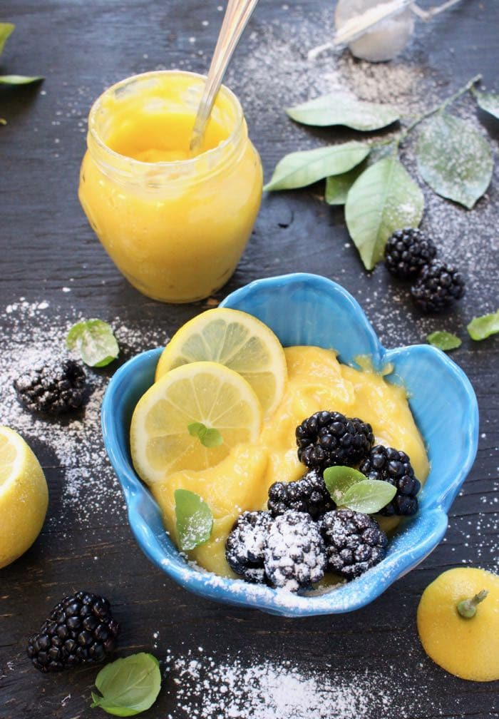 Homemade Lemon Curd in a Jar and a Blue Bowl with Blackberries and Lemon Slices
