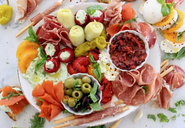 White Marble Platter of Italian Antipasto: cured meats, marinated vegetables, cheese and crostini