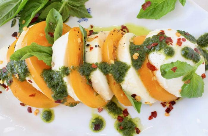 Basil Oil Drizzled over Slices of Yellow Heirloom Tomatoes and Mozzarella di Bufala