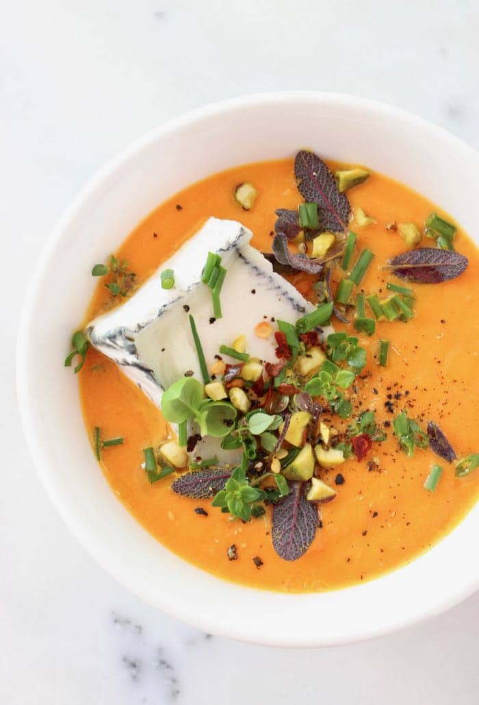 White Bowl of Easy Cream of Carrot Soup with Cheese and Herbs