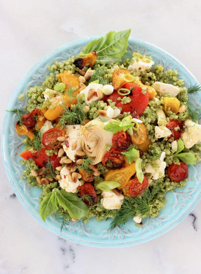 Mediterranean quinoa salad dressed in basil pesto with roasted tomatoes, peppers and artichokes on a blue serving platter
