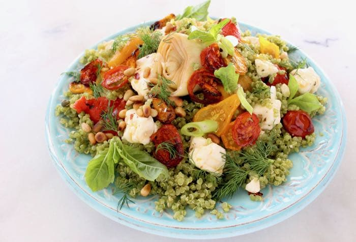 Mediterranean quinoa salad with artichokes, tomatoes and roasted peppers in a blue bowl