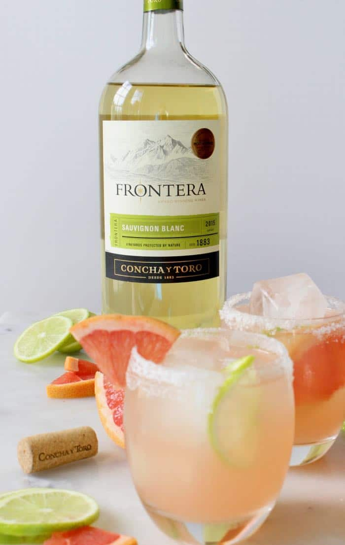 Glasses of Paloma cocktails on ice with sliced grapefruit and limes