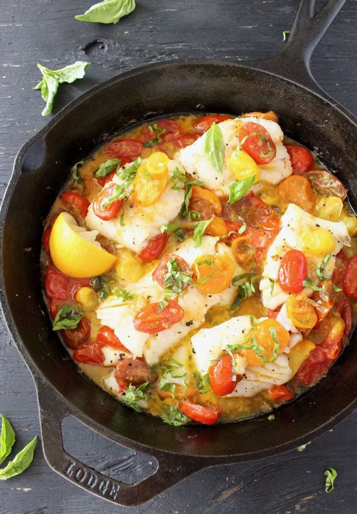 Pan Seared Halibut Fillets in Garlic White Wine Sauce with Heirloom Tomatoes and Basil in a Cast Iron Skillet